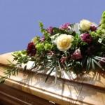 casket with flowers, blue sky