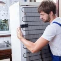 Άνθρωπος κρατάει ψυγείο με τα χέρια του
