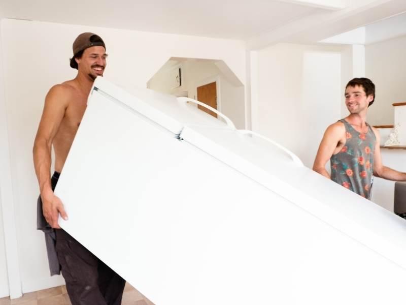 Δυο άνθρωποι μεταφέρουν ένα ψυγείο