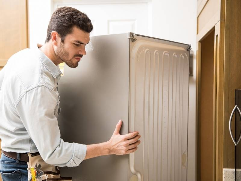 Τεχνικός κρατάει την πλαϊνή πλευρά ψυγείου