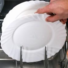Χέρι τοποθετεί άσπρο πιάτο σε πλυντήριο πιάτων